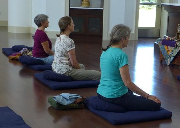 Three women meditate