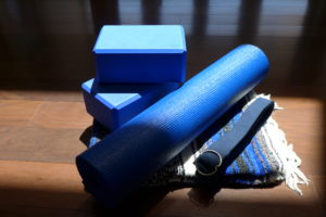 Blue yoga blocks, rolled blue yoga mat, blue yoga sraps, on blue striped yoga blanket
