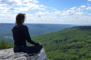 Woman in black sits cross legged in a meditation pose at the edge of a cliff