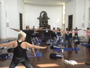 A classroom of yoga students in triangle pose