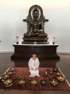 a woman in white sits before a giant copper Buddha, ringed by singing bowls