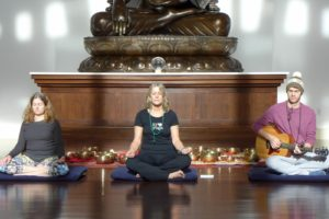 three peopel meditating, one with a guitar