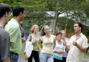Man in white shirt talking to a group of people outdoors