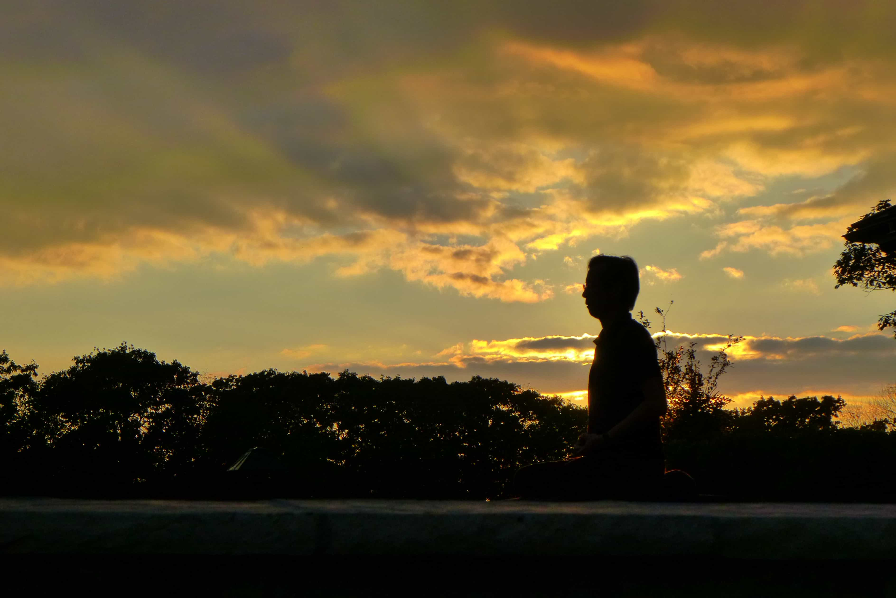 Seated man silhouetted at sunset