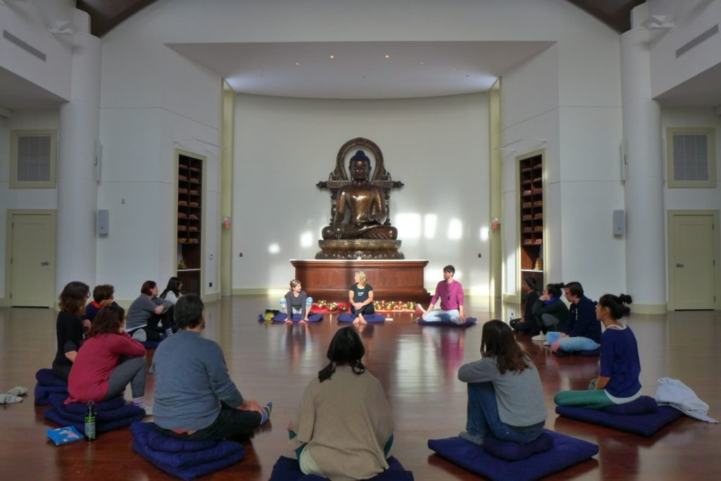 people sit in a large circle in a light filled room with a large Buddha