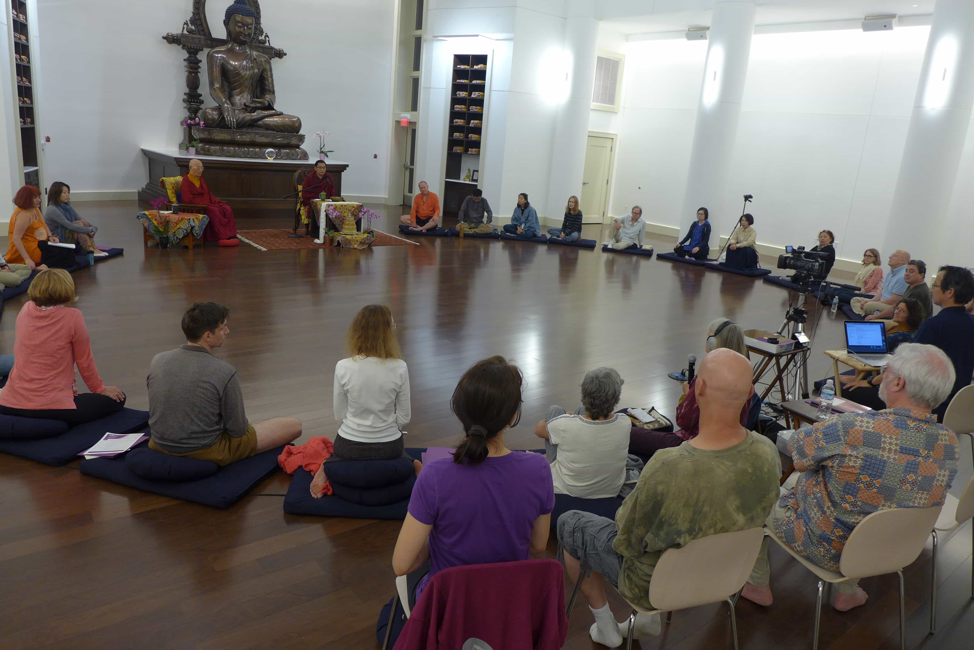 Peopel sitting in a large circle listening to Trungram Gyalwa Rinpoche