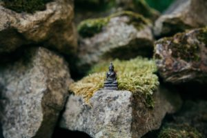 small statue of milarepa on a mossy rock