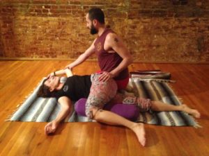 beaded man with topknot helping a woman do yoga