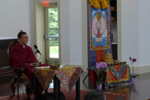 A Buddhist Rinpoche in a chair with Tibetan Buddhist trappings