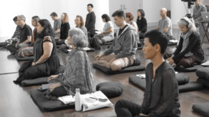 a group of peopel sitting on meditation cushions