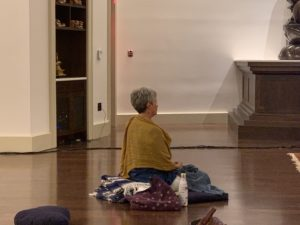 woman sits in meditation hall