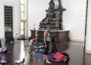 A yoga instructor helps a participant in a yoga class with a large Buddha statue in the back