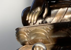 Buddha's fingers touching the ground in a statue