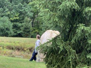 woman leans against a rock in quiet contemplation