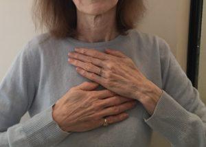 A woman in a blue sweater self heals using Reiki