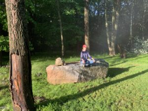 a woman meditates outdoors on a rock