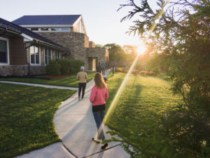 People walk around a coutryard as the sunlight shines