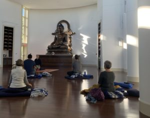 a group of peopel sit in meditation in front of a large statue of Buddha