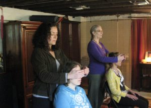 two students stand behind feloow students learning and practicing reiki