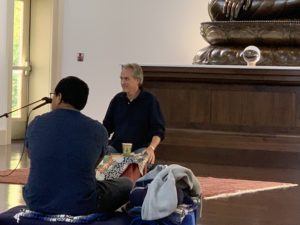 two men sit in a meditation hall