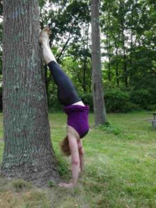 Amy Hamilton does a handstand against a tree