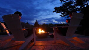 People sitting around a fire pit at dusk